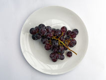 Uvas negras en la placa blanca Foto de archivo