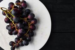 Uvas negras maduras frescas en la placa de servicio de mármol blanca imagen de archivo