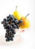 Uvas oscuras y peras amarillas en un florero Imagen de archivo