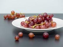 Uvas púrpuras en la placa blanca en la tabla negra Foto de archivo