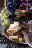 Uvas pretas e verdes, queijo francês, nozes e copo de vinho Foto de Stock Royalty Free