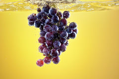Uvas que salpican en el tanque de agua Imagenes de archivo