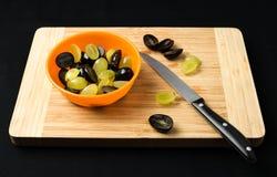 Uvas que son cortadas por la mitad en la tajadera Imagenes de archivo