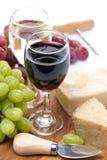 Uvas, queso duro y dos vidrios de vino en el tablero de madera Fotografía de archivo libre de regalías