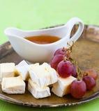 Uvas, queso y miel en una bandeja Fotografía de archivo