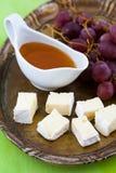 Uvas, queso y miel en una bandeja Foto de archivo