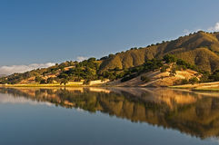 Uvas Reservoir. A morning reflection on Uvas Reservoir of the rolling hills and chaparral of the central California Royalty Free Stock Images