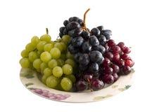 Uvas rojas, blancos y negros frescas en una placa Imágenes de archivo libres de regalías