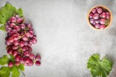 Uvas rojas con las hojas de uvas en una tabla de piedra Visión superior Fre foto de archivo libre de regalías