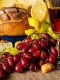 Uvas rojas con un vidrio de vino y de frutas en la tabla Fotos de archivo