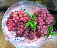 Uvas rojas en el mercado Imagen de archivo libre de regalías