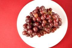 Uvas rojas en la placa blanca Fotografía de archivo