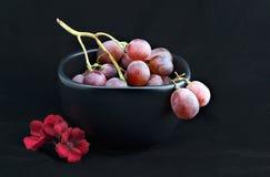Uvas rojas en tazón de fuente negro con la flor Imagenes de archivo