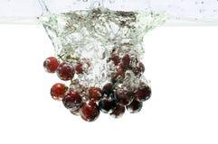Uvas rojas que salpican en el agua Fotos de archivo libres de regalías