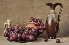 Uvas rojas y mercancías de cerámica Imagen de archivo