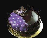 Uvas roxas e bolo de chocolate decorado com beira das videiras do chocolate na pousa-copos dourada fotografia de stock