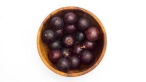 Uvas sin semillas maduras puestas en el cuenco de madera en el fondo blanco almacen de video
