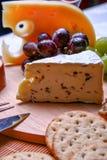 Uvas todavía de la vida del Roquefort del queso, rojas y verdes, galletas en la placa de madera Foto de archivo libre de regalías