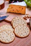Uvas todavía de la vida del Roquefort del queso, rojas y verdes, galletas en la placa de madera Imagen de archivo libre de regalías