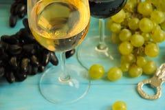 Uvas, um vidro da bebida rústica do vintage do outono do vinho em um backgrounnut de madeira azul imagem de stock