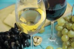Uvas, um vidro do queijo rústico da bebida do outono da porca do vinho em um backgrounnut de madeira azul imagem de stock