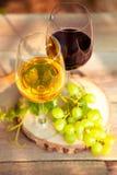 Uvas verdes e dois vidros do branco e do vinho tinto no vi Fotos de Stock Royalty Free