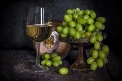 Uvas verdes e um vidro do vinho branco Imagem de Stock
