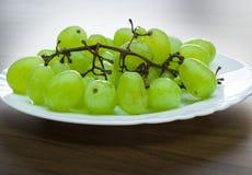 Uvas verdes em uma placa branca na tabela de madeira Imagem de Stock Royalty Free