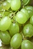 Uvas verdes em uma tabela de madeira imagem de stock royalty free