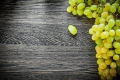 Uvas verdes en concepto de la comida del tablero de madera Imagenes de archivo