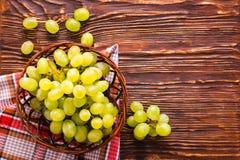 Uvas verdes en la cesta y la servilleta en la tabla de madera Imagen de archivo libre de regalías
