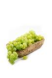 Uvas verdes en la placa de madera Imagen de archivo libre de regalías