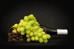 Uvas verdes en una cesta y una botella Imagenes de archivo
