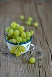 Uvas verdes frescas em uma caneca do vintage fotografia de stock
