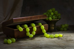 Uvas verdes que cuelgan como un collar de una caja de joyería Foto de archivo