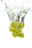 Uvas verdes que salpican en el agua Imagen de archivo