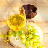 Uvas verdes y dos vidrios del vino blanco y rojo en el VI Imagen de archivo libre de regalías