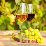 Uvas verdes y dos vidrios del vino blanco y rojo en el VI Imagenes de archivo