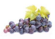 Uvas vermelhas com as folhas isoladas no fundo branco Imagem de Stock