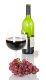 Uvas vermelhas com vidro do vinho e do frasco Imagens de Stock