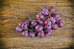 Uvas vermelhas deliciosas maduras na tabela Fotos de Stock