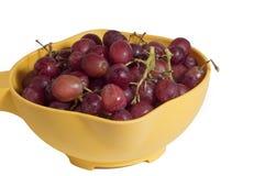 Uvas vermelhas em uma bacia amarela foto de stock