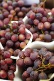 Uvas vermelhas frescas no contador da loja imagens de stock royalty free