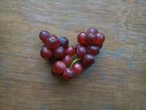 Uvas vermelhas na forma do coração Imagens de Stock Royalty Free