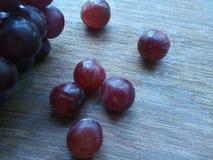 Uvas vermelhas na madeira Imagens de Stock Royalty Free