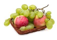 Uvas y manzanas en una cesta de mimbre Fotos de archivo