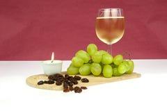 Uvas y pasas del vino blanco con la vela Fotografía de archivo libre de regalías