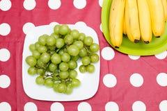 Uvas y plátano en una tabla Imágenes de archivo libres de regalías