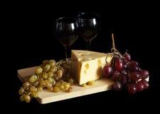 Uvas y queso con los vidrios Imágenes de archivo libres de regalías