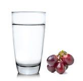 Uvas y vidrio de agua encendido sobre el fondo blanco Imagen de archivo